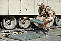 An ammunition specialist carries a 105mm armor-piercing, discarding sabot round, to be used in an M-1 Abrams main battle tank, during Desert Shield.jpg