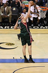 Andrew Bogut lunges toward a rebound while playing for the NBA's Milwaukee Bucks.