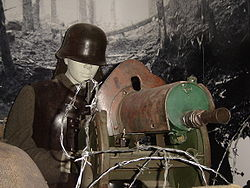 A model of a typical entrenched German machine gunner in World War I. He is operating an MG08, wearing a Stahlhelm and cuirass to protect him from shell fragments, and protected by rows of barbed wire and sandbags.
