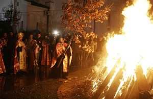 Serbian Christmas traditions - An Orthodox priest places the badnjak on the fire during Christmas Eve celebration at the Cathedral of Saint Sava in Belgrade.