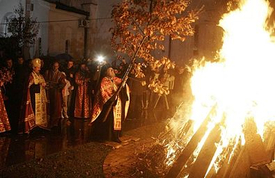 Open-air fire, built with conically arranged long pieces of wood, blazes in the night. Orthodox priest places a long oak sapling with brown leaves on the fire. The priest and the fire are surrounded by a ring of people watching them. In the background, walls of a great church are visible.