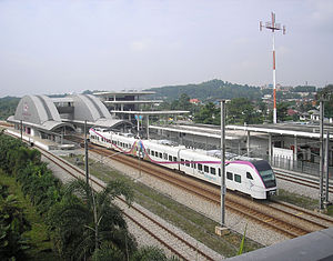 Bandar Tasik Selatan station - An exterior view of the Bandar Tasik Selatan KLIA Transit station southbound, as seen from the footbridge leading to the station. Also depicted is a passing KLIA Ekspres train.