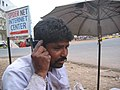 Baramati, Maharashtra, India. A roadside cobbler uses a mobile phone, way back in 2006, a rare happening then.jpg