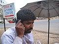 Baramati, Maharashtra, India. A roadside cobbler uses a mobile phone, way back in 2006, a rare happening then.jpg