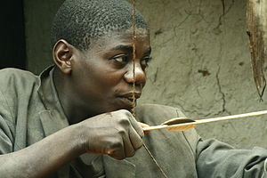 Batwa Pygmy with traditional bow and arrow.