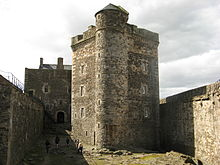 View of castle within its courtyard with a stone building over three stories tall in the middle. The building is flanked by stone walls on both sides that are half as tall.