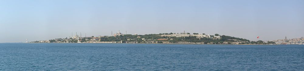 Panoramic view of the historic peninsula of Istanbul, looking westwards from the southern entrance of the Bosporus at the Sea of Marmara. From left to right, the Sultan Ahmed Mosque, the Hagia Sophia and the Topkapı Palace are seen, along with the surviving sections of the Sea Walls of Constantinople. The Galata Tower is seen at the far right of the picture, across the Golden Horn. The arches and vaults of the Byzantine-era Mangana (Armoury) and the Hagios Georgios Monastery which was located inside it are seen between the Blue Mosque and the Hagia Sophia, near the shore. The dome of the Hagia Irene can be seen to the right of the Hagia Sophia.