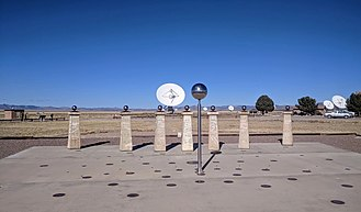 "Very Large Array - The Bracewell Radio Sundial on the VLA walking tour, seen from the south. Named for Ronald N. Bracewell, this sundial marks on the ground positions of the shadow of the central sphere (the gnomon) at different times of day and times of year. The shadow on Dec 22, 2017 falls very near the winter solstice line and the 1:00 PM (solar time) mark.  The other two lines of markers north of the gnomon are for the equinoxes and the summer solstice.  Additional lines of markers south of the gnomon mark positions of ""shadows"" of the radio sources Cygnus A and Cassiopeia A. The posts at the back of the sundial were recovered from Bracewell's radio telescope array at Stanford University, abandoned in 1980, where they had been signed by visitors with chisels at his invitation."