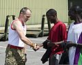 British Army Warrant Officer Class 2 Doug Herbert, left, with the Allied Rapid Reaction Corps (ARRC), presents Malawian Olympic athletes with ARRC 300 T-shirts at Imjin Barracks, Innsworth, Gloucester, United 120712-O-ZZ999-004.jpg