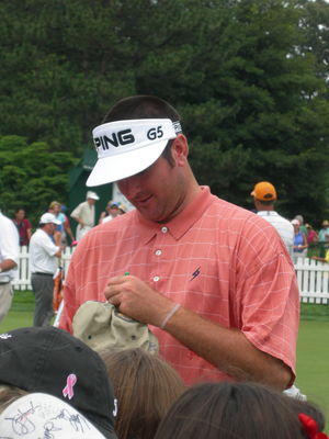 Bubba Watson signing autographs on the putting...