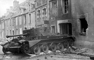 A tank, with debris strewn around it, is in front of a damaged and fire scorched house. The tank is partly on the pavement and partly on the road.