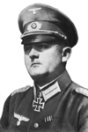 A man wearing a peaked cap and military uniform with an Iron Cross displayed at the front of his uniform collar.