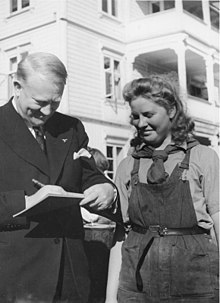 A middle-aged man in a dark coloured suit is writing on a pad of paper. Standing close to him and watching is a woman in her late twenties to earlier thirties. She is smiling, and wearing dark coloured dungarees, with a shirt underneath and a scarf tied around her neck.