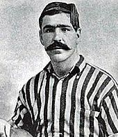 Head and upper torso of a young dark-haired white man with thick eyebrows and a large moustache. He is looking straight ahead, and is wearing a tasselled cap and open-necked striped shirt.
