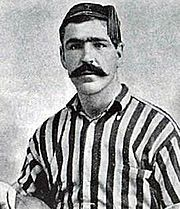 A black-and-white photograph of footballer Caesar Jenkyns, wearing a vertically-stripped shirt.