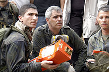 Three men, one of whom is holding a partially mangled red metal box