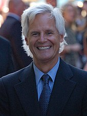 A man with long white hair and a black suit, with a tie, is called Chris Carter creator of The X Files TV Show about Aliens and UFOs