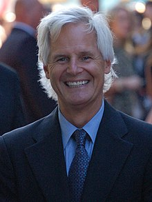 A man with long white hair and a black suit, with a tie, is standing and smiling.