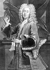 Black and white image of a man facing centre. He is wearing a shoulder length wig, has an elaborate coat with a cloth around his neck. He has a hat under his left arm and both a glove and a watch in his left hand. He is holding up his right hand with the thumb and pointer pressed together.