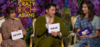 "Constance Wu, Henry Golding, and Gemma Chan hold white cards with ""never"" and ""have"" on them"