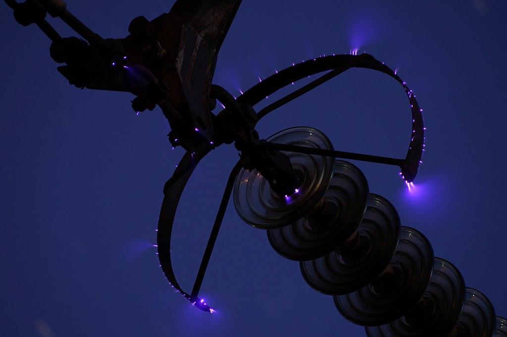Фото на довгій витримці коронного розряду на захисному кільці високовольтної лінії передач. Фото з Вікіпедії на умовах CC BY-SA 3.0