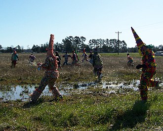 Courir de Mardi Gras - Chasing a chicken through a muddy field