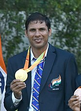 A photograph of a man wearing blue coloured suit with gold medal in his right hand.