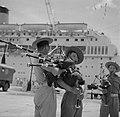 Doedelzakspelers in de haven van Tandjong Priok Op de achtergrond de MS Oranje , Bestanddeelnr 254-5389.jpg