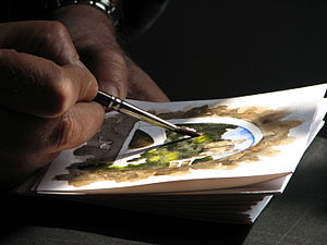 Artist working on a watercolor using a round brush.