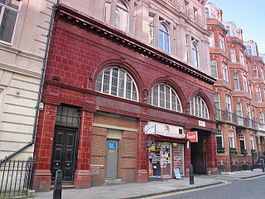 Station building faced in red glazed blocks with three large semi-circular windows at first floor level. Part of the ground floor is occupied by a shop and part has been bricked-up with a small service door