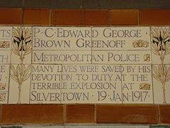 "A tablet formed of five tiles of varying sizes, bordered by yellow wheatsheaves in an art nouveau style. The tablet reads ""P.C. Edward George Brown Greenoff, Metropolitan Police. Many lives were saved by his devotion to duty in the terrible explosion at Silvertown 19 Jan 1917""."