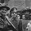 Een Britse militair getooid met een Duitse officierspet een andere voert een po, Bestanddeelnr 900-2386.jpg
