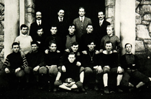 An old black and white photograph of eighteen male student members dressed in football gear