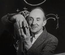 Photograph of the head, shoulders, and hands of a man standing in front of a blackboard. The man is smiling and staring at this hands, which are at to the left of his face in the photograph; he is apparently using his hands to explain something. The fingers of his left hand are pointing upwards. His right hand is above his left, with its fingertips pointing downwards and touching the matching fingertips of his left hand. The two hands thus form an enclosure. He is dressed in a tweed jacket with a necktie. There is a diagram chalked on the blackboard.