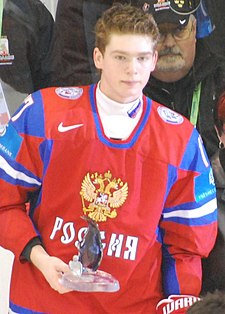 A short- and light brown-haired caucasian male in a red, Russian, ice hockey uniform is holding a small glass award.