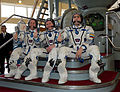 Expedition 31 backup crew members in front of the Soyuz TMA spacecraft mock-up in Star City.jpg