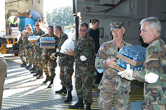 Georgia State Defense Force - Members of the Georgia Defense Force rapidly unload a supply of water and ice at Dobbins AFB in anticipation of a flight from New Orleans containing hurricane Katrina evacuees.