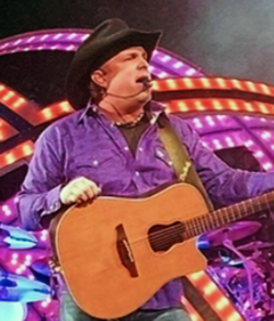 Garth Brooks performing on stage, while holding a guitar.