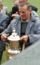 A middle aged man wearing shirt, grey pullover and light grey anorak, holding a trophy cup. other people behind him, all standing on grass. Bottom right of picture cut off by a wall.