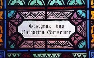 """Roman Catholic Archdiocese of Dubuque - Panel in the church's window donated by Catharina Gansemer (1824-1904), an early parishioner and area pioneer. """"Geschenk von"""" means """"gift of."""" Photo by Joe Schallan, 2003."""