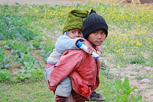 Piggyback (transportation) - A Nepali child carries another child piggyback.