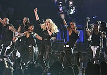 Image of Madonna and several dancers wearing glasses and black baggy outfits dancing along.
