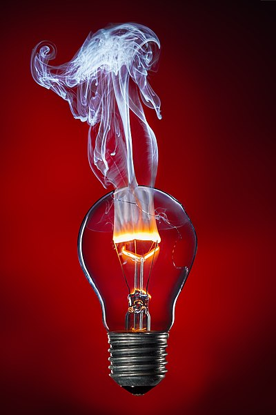 The glass bulb of the lightbulb has been opened, causing the inert gas inside to escape. When turned on, the tungsten filament burns with a flame, due to oxygen entering the light bulb. The light bulb was screwed into a socket, which was replaced with the lamp base using image processing.