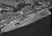 """Aerial photograph taken from directly overhead of a small aircraft carrier, while she is berthed alongside a wharf. Nine aircraft are parked in a three-by-three pattern at the carrier's stern, and personnel are positioned to spell out the word """"Aloha"""" when seen from above."""