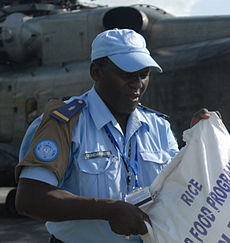Haitian police with rice bag and UN brassard.jpg