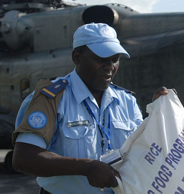 Haitian police with rice bag and UN brassard.jpg
