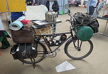 A profile of Heinz Stücke's black bicycle, laiden with baggage and a bedroll. Behind it, Stücke talks with two visitors.