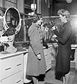 Hilda Chillingworth (left) looks at hats in a shop during her lunch brea in London during 1942. D12068.jpg