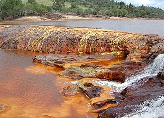 Banded iron formation - Water flowing over iron-rich beds in Rio Tinto, Spain