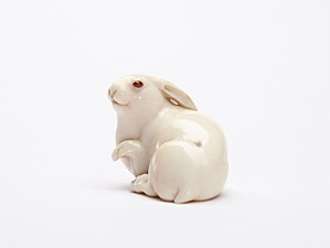 Netsuke - The Hare with Amber Eyes netsuke, by Masatoshi, Osaka, ca. 1880, signed. Ivory, amber buffalo horn.